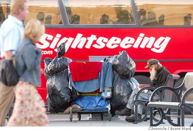 At Fisherman's Wharf, sightseeing buses are a common sight, and homeless persons and their carts are showing up in increasing numbers. Here Eddie sits and reads a book late in the day...he has been on the streets for over two years. BRANT WARD / The Chronicle Photo: BRANT WARD