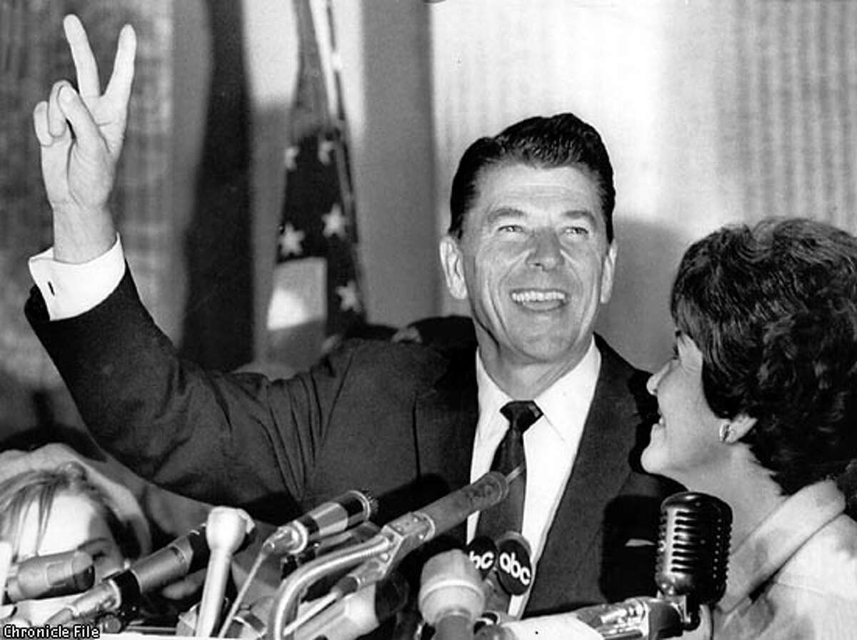 Ronald Reagan flashes the victory sign after he won the governorship of California over incumbent democratic governor Edmund G. (Pat) Brown. Reagan's wife, Nancy, is at right.