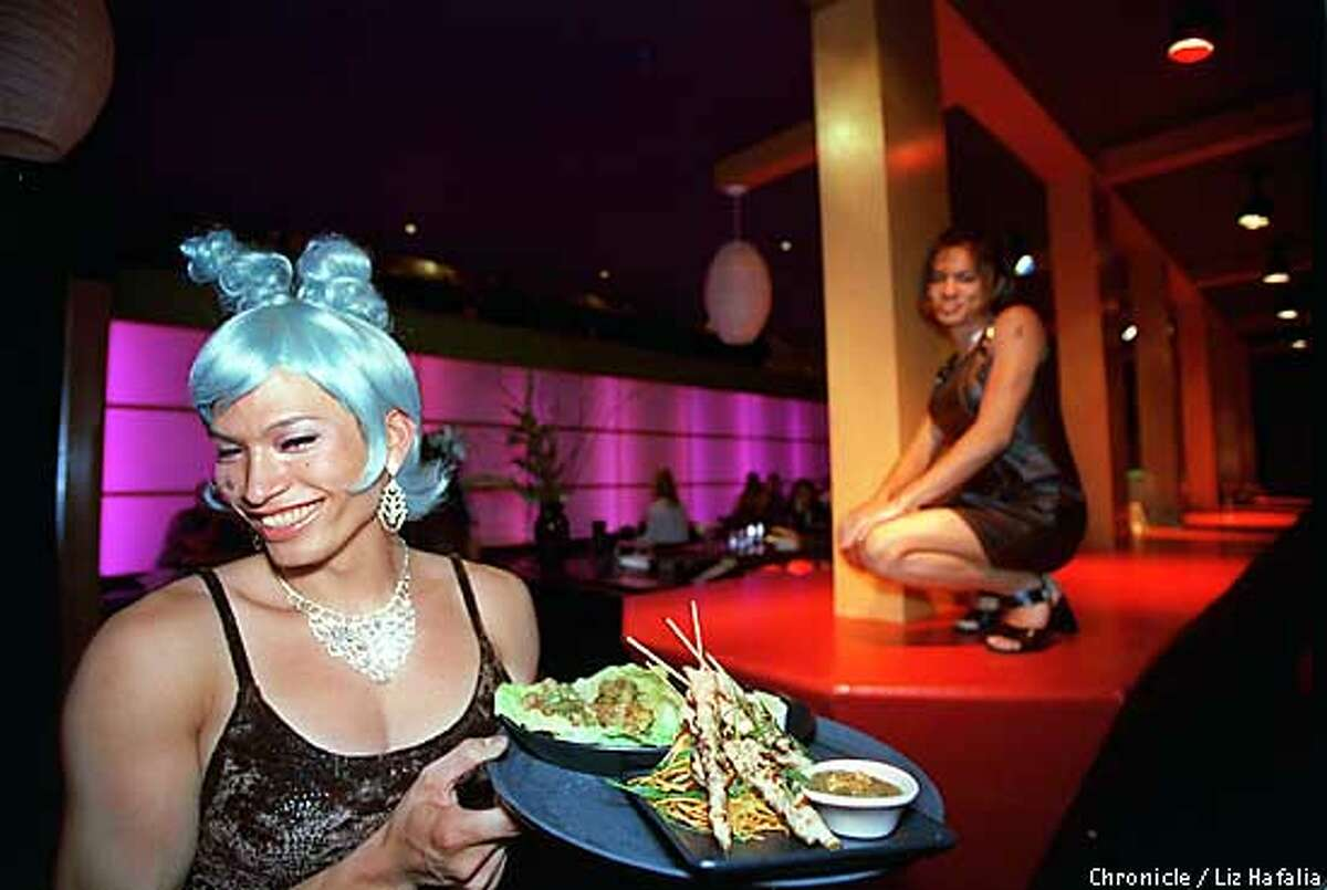D.21 ASIASF/C/11JUN98/PK/LH--Coco (has blue hair), a waitress at asiaSF brings out a tamarind chicken satay and spicy minced chicken. Waitress and dancer, Kiana at right. Photo by Liz Hafalia