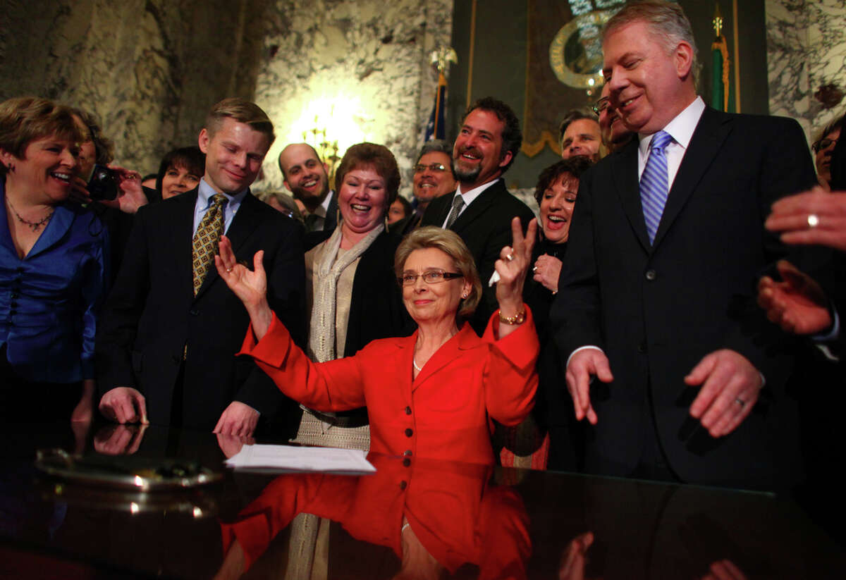 Gov. Chris Gregoire celebrates with legislators after signing a bill legalizing gay marriage in Washington on Monday at the Legislative Building of the Washington State Capitol in Olympia. At left is state Rep. Jamie Pedersen and at right is state Sen. Ed Murray.