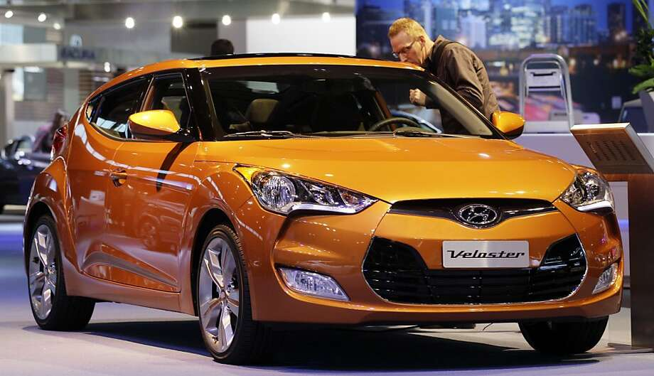 A visitor looks ovea the Hyundai Veloster during the media preview of the Chicago Auto Show at McCormick Place in Chicago, on Thursday, Feb. 9, 2012. (AP photo/Nam Y. Huh) Photo: Nam Y. Huh, Associated Press