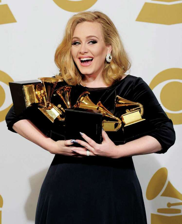 """Adele poses backstage with her six awards at the 54th annual Grammy Awards on Sunday, Feb. 12, 2012 in Los Angeles. Adele won awards for best pop solo performance for """"Someone Like You,"""" song of the year, record of the year, and best short form music video for """"Rolling in the Deep,"""" and album of the year and best pop vocal album for """"21."""" (AP Photo/Mark J. Terrill) Photo: Mark J. Terrill"""