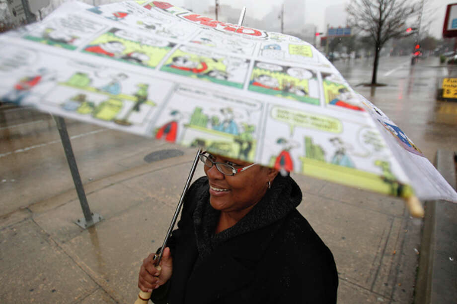 Doris Ross stands in the cold rain as she waits for public transportation along Congress St. in downtown on Monday, Feb. 13, 2012, in Houston. (Mayra Beltran / Houston Chronicle)