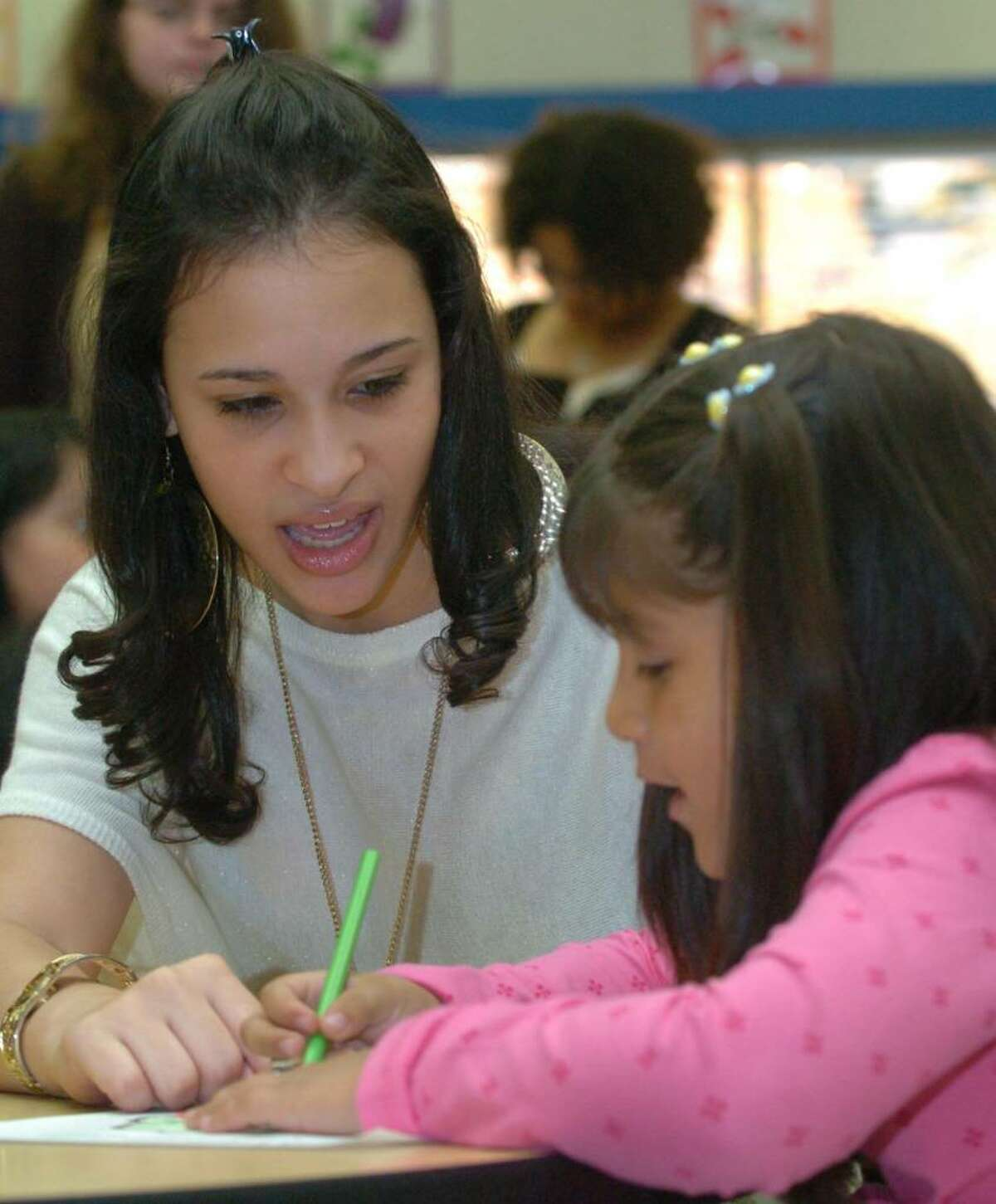 From left, Crisannys Fernandez, 15 works with Ashley Arias of King St Primary school durning a lesson at Danbury High School, Thursday, Oct. 29, 2009.