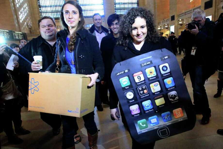 Sarah Ryan, left, and Shelby Knox with Change.org, arrive at the Apple store in New York to deliver petitions asking Apple to address conditions in its China factories. Apple said Monday the Fair Labor Association is inspecting the plants. Photo: Mary Altaffer / AP