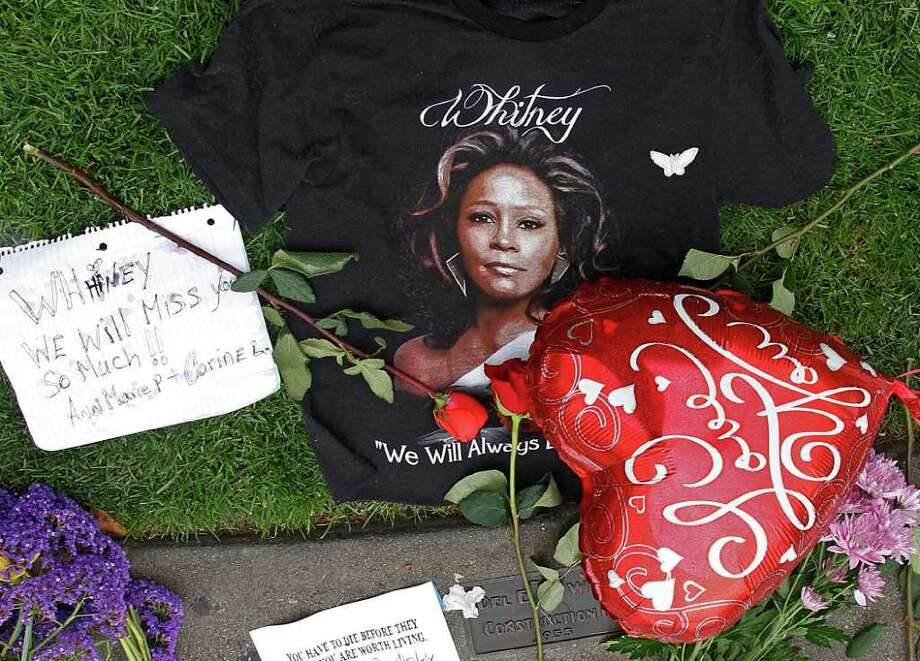 A T-shirt, flowers and notes are left at a makeshift memorial for Whitney Houston outside the Beverly Hills Hilton Hotel in Beverly Hills, Calif., Monday, Feb. 13, 2012. Houston, who ruled as pop music's queen until her majestic voice and regal image were ravaged by drug use, erratic behavior and a tumultuous marriage to singer Bobby Brown, died Saturday, Feb. 11. She was 48.  (AP Photo/Damian Dovarganes) Photo: Damian Dovarganes