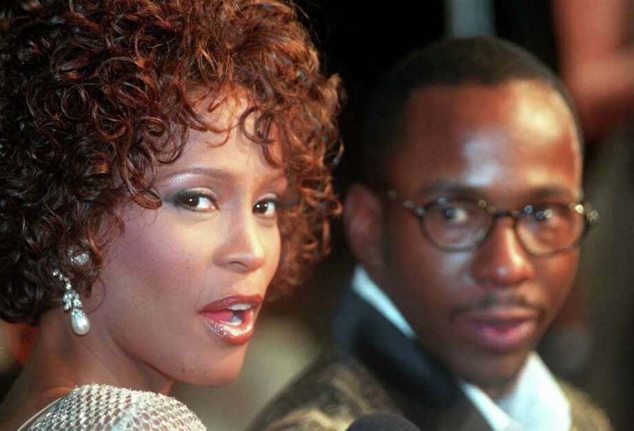"FILE - In this Oct. 13, 1997 file photo, Whitney Houston looks over her shoulder as her husband Bobby Brown looks to her at the premiere of ""The Wonderful World of Disney"" movie ""Cinderella,"" at Mann's Chinese Theater in the Hollywood section of Los Angeles, Whitney Houston, who reigned as pop music's queen until her majestic voice and regal image were ravaged by drug use, has died, Saturday, Feb. 11, 2012. She was 48. (AP Photo/Rene Macura, File) Photo: RENE MACURA, ASSOCIATED PRESS / AP1997"
