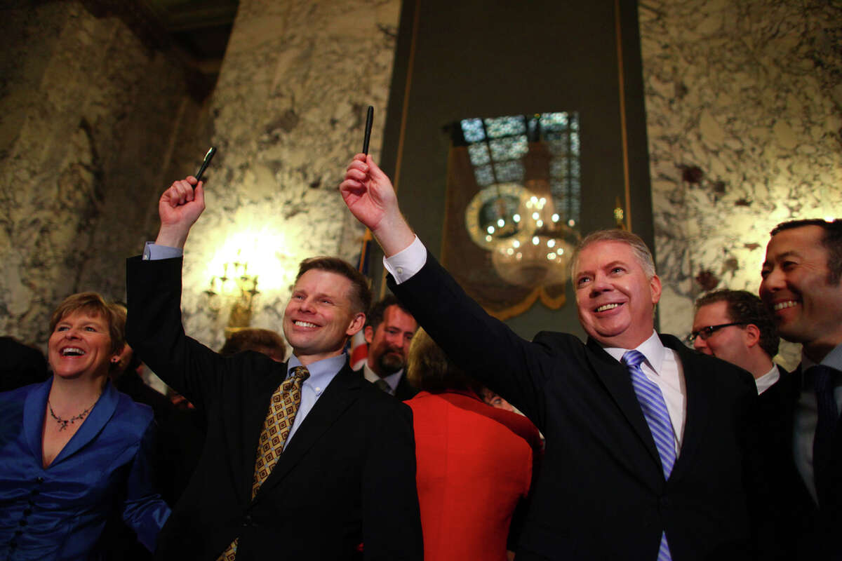 Rep. Jamie Petersen and Sen. Ed Murray raise pens used by Gov. Chris Gregoire to sign a bill legalizing gay marriage in Washington on Monday at the Legislative Building of the Washington State Capitol in Olympia.