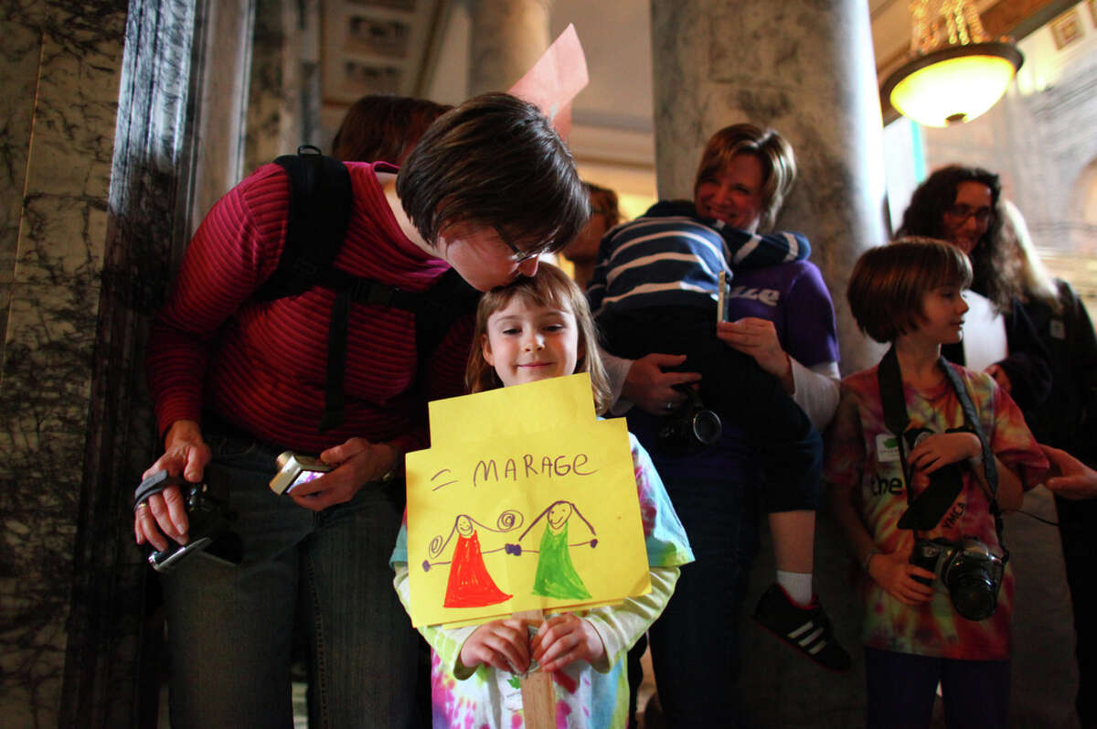 Katherine Haycox, 6, of Seattle, is kissed on the head by her mom Jane Wiebe after a bill was signed legalizing gay marriage in Washington State on Monday February 13, 2012 at the Legislative Building of the Washington State Capitol in Olympia.
