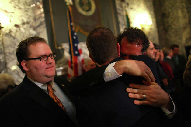 Sen. Kevin Ranker, right, is hugged by another legislator after a bill was signed legalizing gay marriage in Washington State on Monday February 13, 2012 at the Legislative Building of the Washington State Capitol in Olympia. At left is Rep. Marko Liias. Photo: JOSHUA TRUJILLO / SEATTLEPI.COM