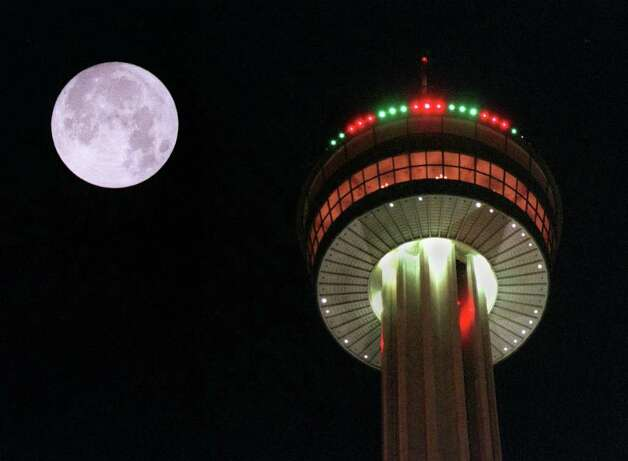 A full moon looms above the Tower of the Americas, one of San Antonio's most romantic spots. Photo: KRISTA NILES, SPECIAL TO THE EXPRESS-NEWS