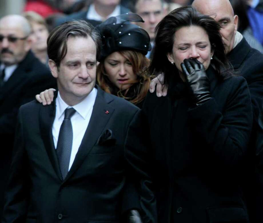 Matthew Badger, left, and Madonna Badger, the parents of three children that were killed in a fire, react as their caskets are carried into a church during the funeral in New York, Thursday, Jan. 5, 2012. Hundreds of people streamed into a historic church in the heart of Manhattan on Thursday for the funeral of three young girls who died along with their grandparents during a Christmas morning fire in Stamford, Conn.  (AP Photo/Seth Wenig) Photo: Seth Wenig, Associated Press / AP