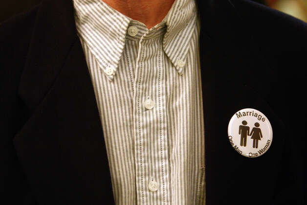An opponent of Washington State's gay marriage bill wears a button on Monday ...