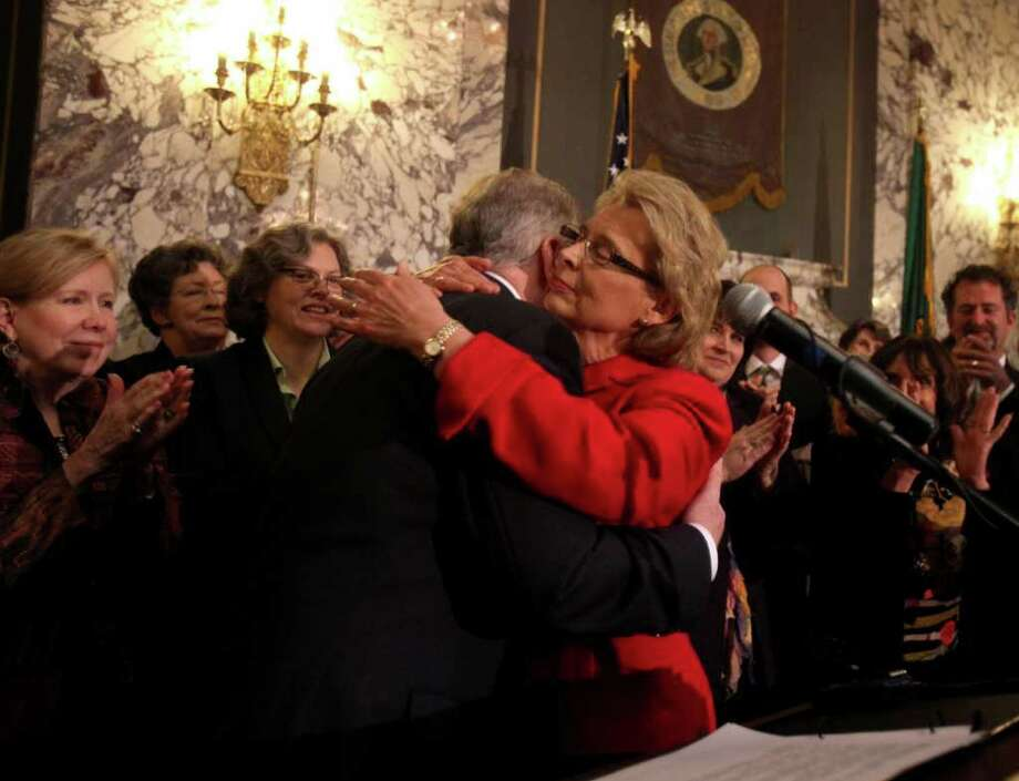 Washington Gov. Chris Gregoire hugs Sen. Ed Murray before signing a bill Monday allowing same-sex couples to marry.  The law takes effect June 7. Photo: Steve Bloom / The Olympian