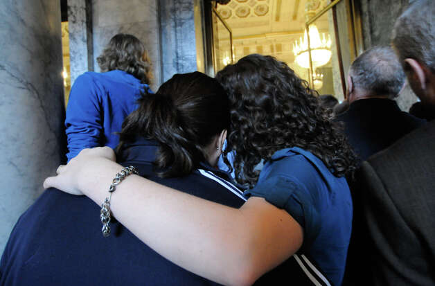 Two women hold each other as they look into the State Reception Room where same-sex marriage is being signed into the law by Gov. Gregoire last February. Opponents put the law on the ballot.  Referendum 74 is on Tuesday's ballot.. Photo: LINDSEY WASSON / SEATTLEPI.COM