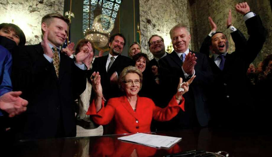 Washington Gov. Christine Gregoire, seated, raises her arms as legislators and supporters cheer behind her after she signed into law a measure that legalizes same-sex marriage Monday, Feb. 13, 2012, in Olympia, Wash. Gregoire handed gay rights advocates in Washington state a major victory with her signature, making it the seventh in the nation to allow gay and lesbian couples to wed. The law takes effect June 7, but opponents are already mounting challenges on multiple fronts. (AP Photo/Elaine Thompson) Photo: Elaine Thompson