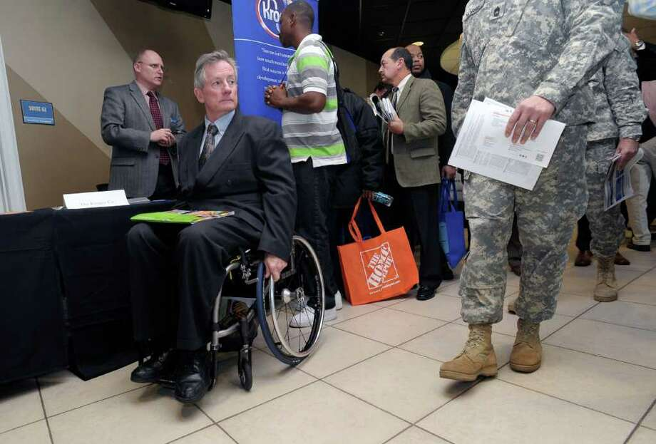 FILE - In this Feb. 9, 2012 file photo, disabled army veteran Ken Higgins, of Lilburn, Ga., finishes with a recruiter as he and other veterans attend a military-to-civilian job and education fair held at Turner Field, in Atlanta. General Electric Co. plans to hire 5,000 veterans over the next five years and invest $580 million to expand its aviation business. (AP Photo/John Amis, File) Photo: John Amis / FR69715 AP