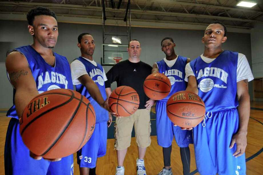 Bishop Maginn boys basketball coach Rich Gilooly, center, stands with players Rushon Young, left, Aljamar Mathis, second from left, Derek Thomas, second from right, Demere Hannah, right, after practice at the school on Monday Feb. 13, 2012 in Albany, NY.  (Philip Kamrass / Times Union ) Photo: Philip Kamrass / 00016411A