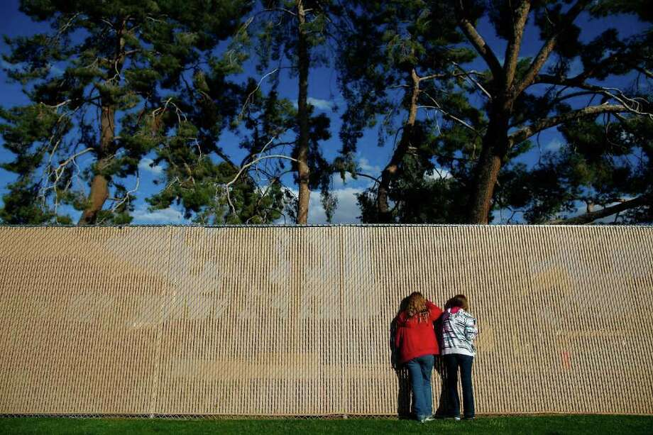 Two girls look through a fence into the amphitheater before Republican Massachusetts Gov. Mitt Romney attends a Get out the Vote.( Eric Thayer / Getty Images ) Photo: Eric Thayer, Getty Images / 2012 Getty Images
