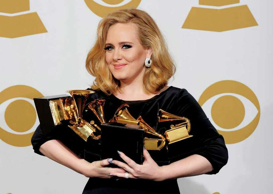 "Adele poses backstage with her six awards at the 54th annual Grammy Awards on Sunday, Feb. 12, 2012 in Los Angeles. Adele won awards for best pop solo performance for ""Someone Like You,"" song of the year, record of the year, and best short form music video for ""Rolling in the Deep,"" and album of the year and best pop vocal album for ""21."" Photo: AP"