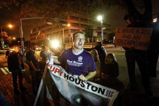 Carl Gibson, center, and other participants in the Occupy Houston movement march at Tranquillity Park after police officers cleared the park after sunset Monday on Mayor Annise Parker's orders. Photo: Michael Paulsen / © 2012 Houston Chronicle