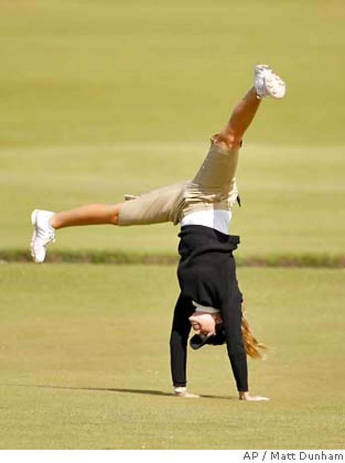 Paula Creamer of the U.S. performs a cartwheel on the 18th hole as she poses for a photographer after a Pro Am event ahead of the Women's British Open golf tournament at the Old Course at the Royal and Ancient Golf Club in St Andrews, Scotland, Wednesday, Aug. 1, 2007. The tournament begins on Thursday. (AP Photo/Matt Dunham) ** EDITORIAL USE ONLY ** EDITORIAL USE ONLY Photo: MATT DUNHAM