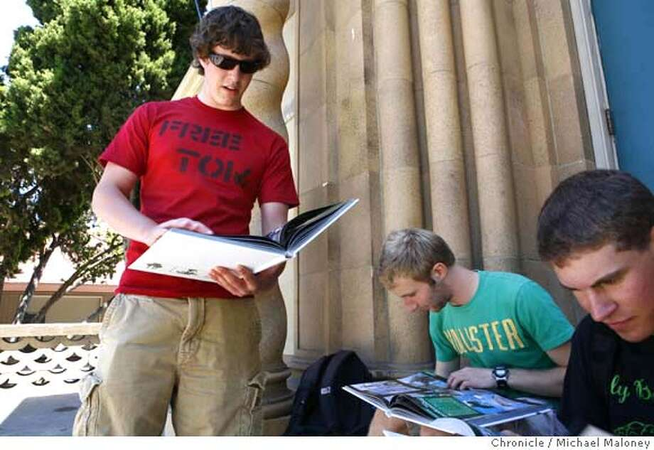 """From left, students Jeremy Carlson, Zev Karlin-Neumann and Carey Schwartz look over the yearbooks that were distributed today. Carlson wears a """"Free Tom"""" t-shirt in protest to his friend Daniel Blaine Marchant's arrest. """"Tom"""" is in reference to Marchant's sometimes used nickname. Police arrested Palo Alto High School senior Daniel Blaine Marchant on Tuesday on suspicion of felony vandalism as well as a misdemeanor -- defacing the vehicle identification number on his 1994 Volvo station wagon so it couldn't be traced to him.  Officers found the car upside down, spray-painted with multiple colors, the hood and tires missing and resting in the middle of the school quad area.  Photo by Michael Maloney / San Francisco Chronicle Photo taken on 6/7/07 in Palo Alto, CA  *** Daniel Blaine Marchant, Jeremy Carlson, Zev Karlin-Neumann, Carey Schwartz Photo: Michael Maloney"""