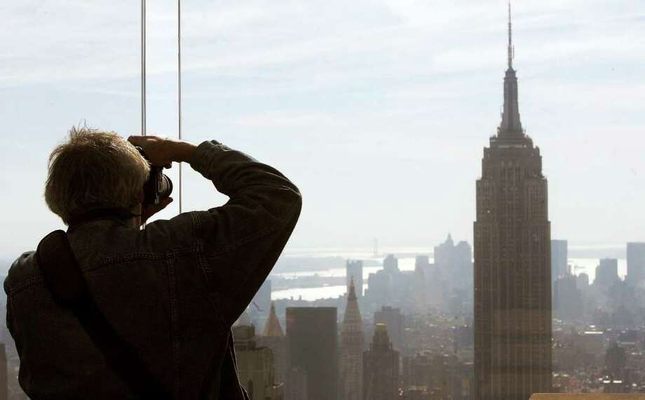A visitor photographs the Empire State Building from Rockefeller Center. Empire State Realty Trust says it needs $55 million to $65 million beyond 2013 to complete its upgrades of the famed tower. Photo: Mario Tama / Getty Images North America