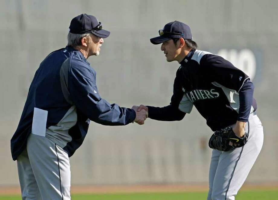 The Seattle Mariners, in Peoria, Ariz., were the first team to open spring training, and new pitcher Hisashi Iwakuma wasted no time greeting and getting to know Dwight Bernard, who is Seattle's Class AAA pitching coach. Photo: Charlie Riedel / AP