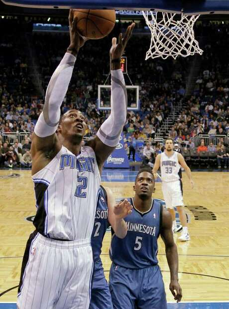 Orlando Magic's Dwight Howard (12) goes up for a shot over Minnesota Timberwolves' Kevin Love and Martell Webster (5) during the first half of an NBA basketball game Monday, Feb. 13, 2012, in Orlando, Fla. Photo: AP