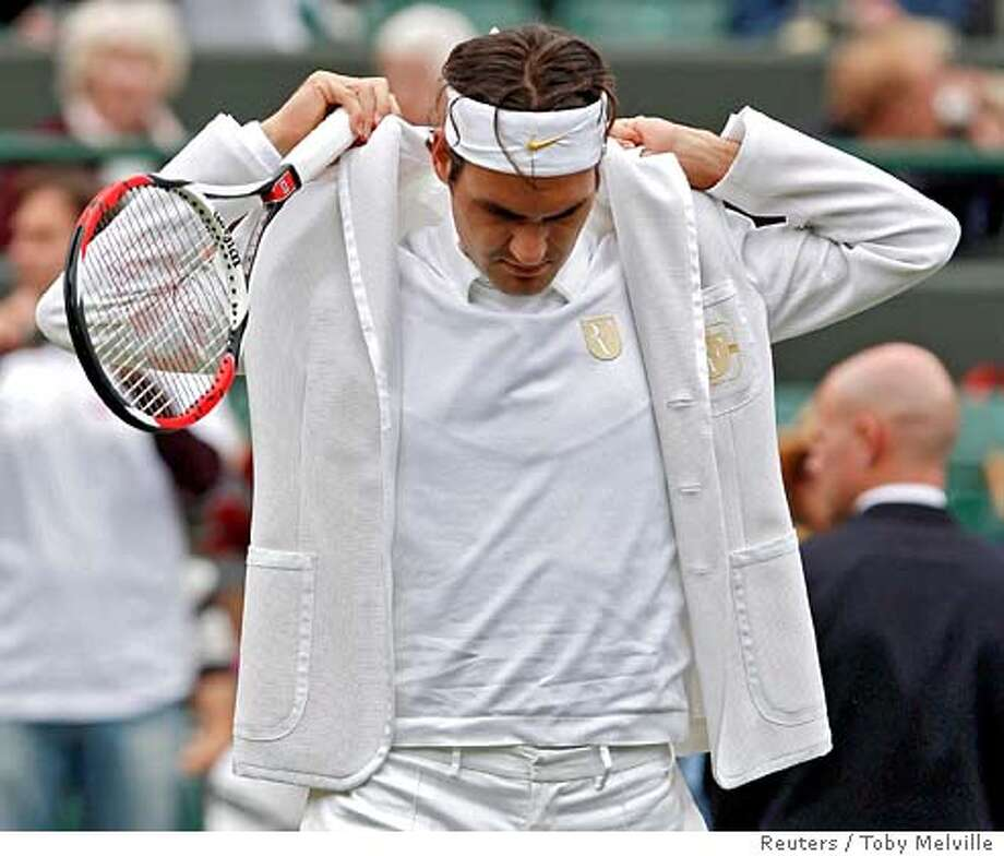 Switzerland's Roger Federer adjusts his jacket during his warm up for his singles match against Argentina's Juan Martin Del Potro at the Wimbledon tennis championships in London, June 27, 2007. REUTERS/Toby Melville (BRITAIN) Photo: TOBY MELVILLE
