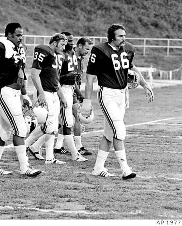 St. Louis Cardinals' Conrad Dobler (66) leads the march off the field at the end of practice at the Cardinals' training camp at St. Charles, Missouri, Aug. 5, 1977. Dobler is followed by running back Jim Otis (35), running back Wayne Morris (24) and coach Don Coryell. (AP Photo) Photo: Ap 1977