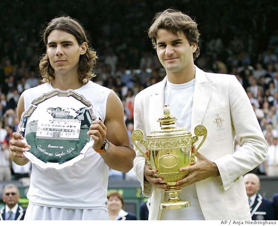 Defending champion Roger Federer, right, holds the winners trophy with runner up Rafael Nadal of Spain after the Men's Singles final on the Centre Court at Wimbledon, Sunday July 9, 2006. Federer won the match 6-0, 7-6, 6-7, 6-3. (AP Photo/Anja Niedringhaus) EDITORIAL USE ONLY Photo: ANJA NIEDRINGHAUS