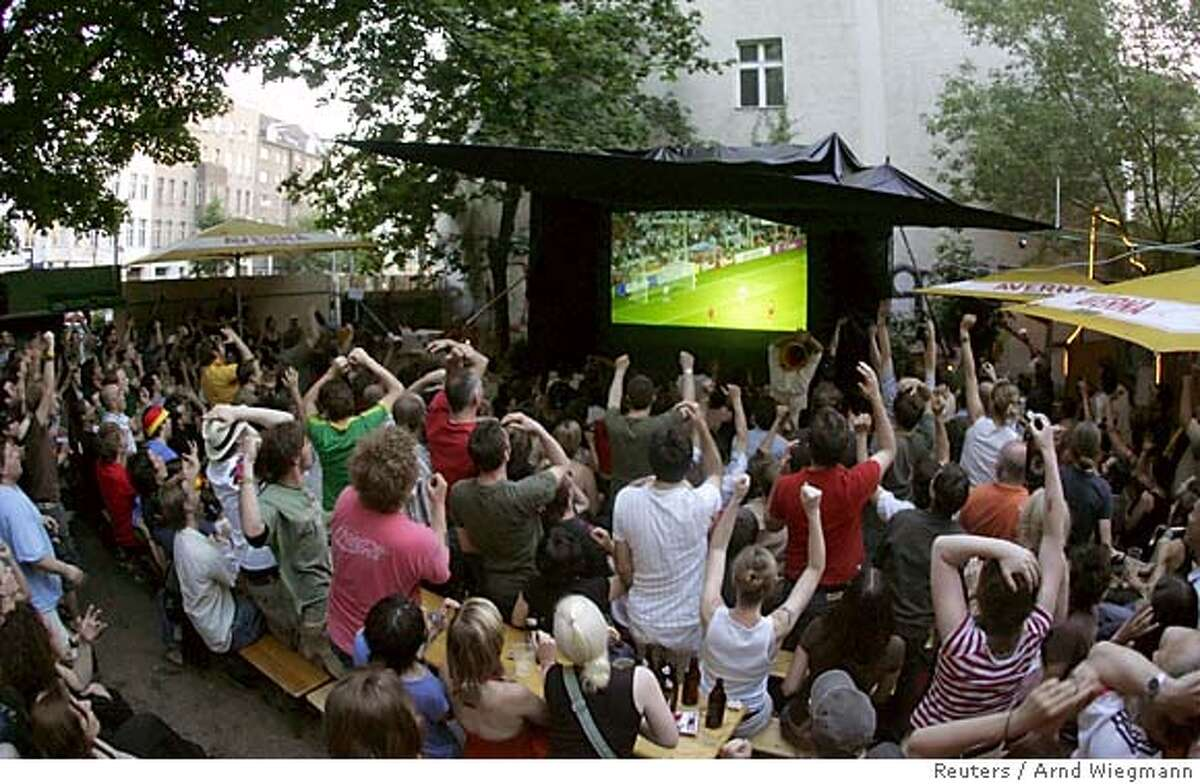 Soccer fans watch the Group A match of the World Cup Germany against Poland on a TV screen in a beer garden in Berlin
