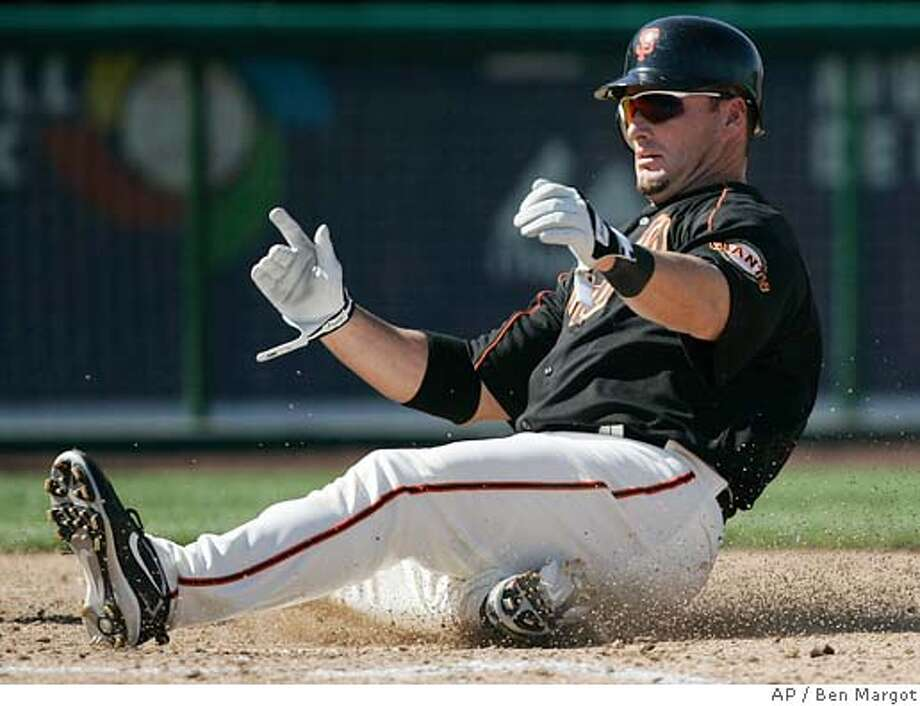San Francisco Giants' Mark Sweeney slides as he scores against the Milwaukee Brewers on a hit by teammate Todd Linden during the fourth inning of a baseball spring training game Friday, March 3, 2006, in Scottsdale, Ariz. (AP Photo/Ben Margot) Photo: BEN MARGOT