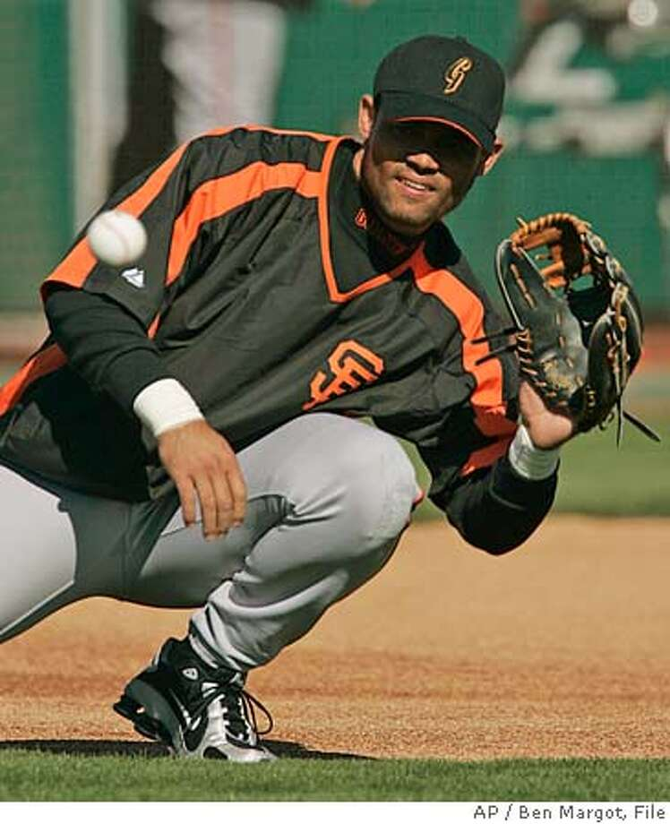 San Francisco Giants third baseman Pedro Feliz fields a ball during a baseball spring training workout Wednesday, Feb. 22, 2006, in Scottsdale, Ariz. After spending most of his career bouncing around from position to position, changing gloves nearly as often as some people change socks, Feliz has the opportunity to play every day at his natural position of third base. (AP Photo/Ben Margot) A WEDNESDAY, FEB. 22, 2006, PHOTO EFE OUT Photo: BEN MARGOT