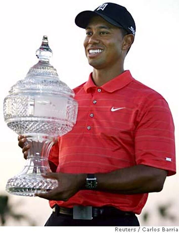 Tiger Woods holds the winner's trophy at the Doral Championship golf tournament in Miami, Florida March 5, 2006. REUTERS/Carlos Barria 0 Photo: CARLOS BARRIA