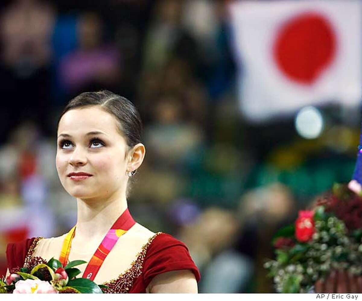 Silver medalist Sasha Cohen of the United States listens to the Japanese national anthem during medal ceremonies at the Women's Figure Skating final at the Turin 2006 Winter Olympic Games in Turin, Italy, Thursday, Feb. 23, 2006. Japan's Shizuka Arakawa won the gold and Russia's Irina Slutskaya the bronze medal. (AP Photo/Eric Gay)