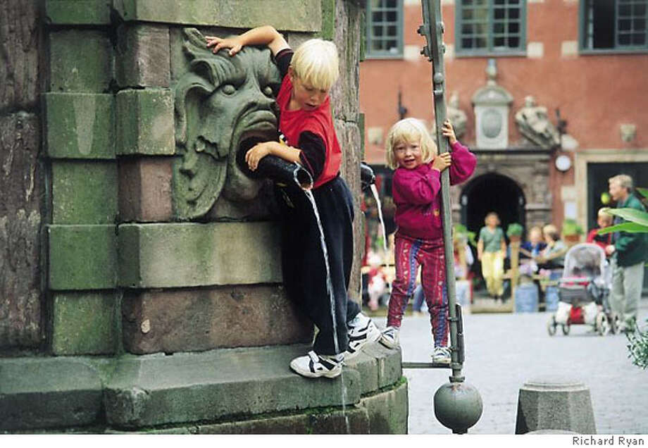 TRAVEL STOCKHOLM -- Children play on a fountain in Stortorget Square. Photo: Richard Ryan