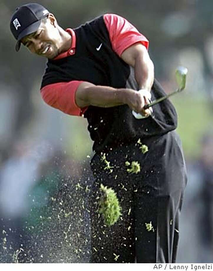 Tiger Woods tears up the turf as he hits a low knockdown shot into the first hole during the final round of the Buick Invitational golf tournament Sunday Jan. 29, 2006, in San Diego Woods started the day one shot back and was one-over-par through the first eight holes. (AP Photo/Lenny Ignelzi) Photo: LENNY IGNELZI