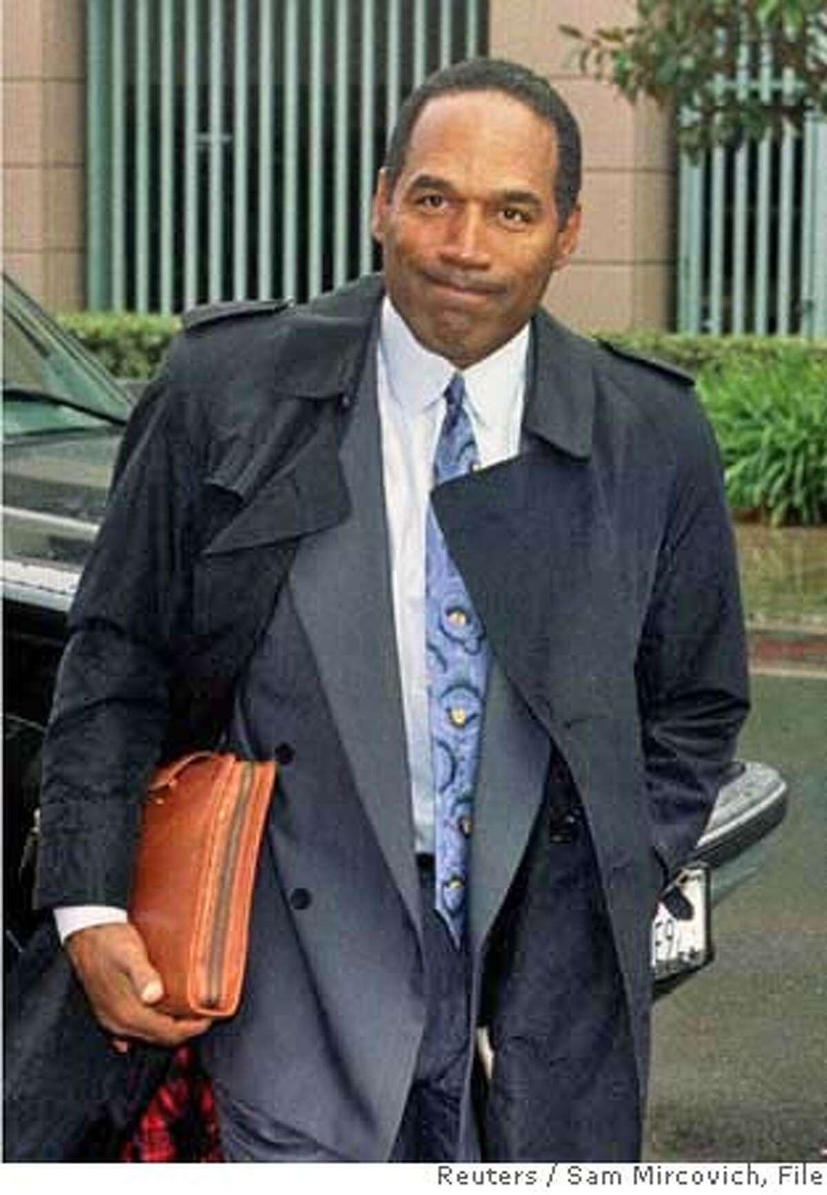 O.J. Simpson arrives at family court for a child custody case in Santa Ana, California in this November 21, 1996 file photo. More than a decade after he was acquitted of charges he murdered his ex-wife Nicole Brown Simpson and her friend Ron Goldman, O.J. will describe in a televised interview how he would have committed the crime if he was the one responsible in a special to air on the Fox Network November 27 and 29, 2006. REUTERS/Sam Mircovich/Files (UNITED STATES) RC/ELD 0