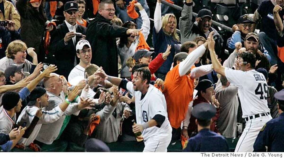 Tigers Sean Casey and Jason Grilli high-five fans as they celebrate clinching a berth in the American League Championship Series Oct. 7, 2006 at Comerica Park. The Tigers defeated the Yankees 8-3. (Dale G. Young / The Detroit News) 2006. DETROIT OUT