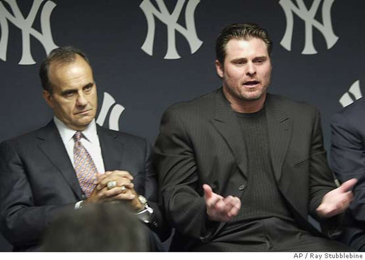New York Yankees first baseman Jason Giambi, right, gestures as he talks to the media Thursday, Feb. 10, 2005 at Yankee Stadium in New York. At left is Yankees manager Joe Torre. (AP Photo/Ray Stubblebine, Pool)