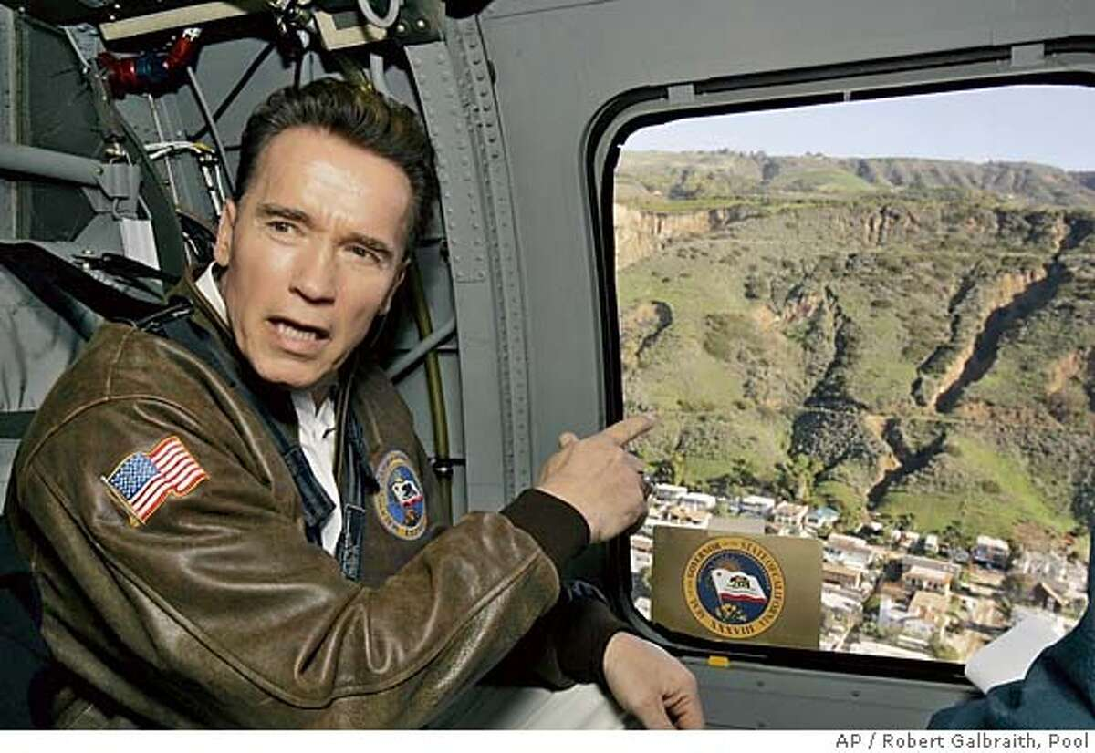 California Gov. Arnold Schwarzenegger talks during a helicopter tour Wednesday, Jan. 12, 2005, over the site of Monday's hillside collapse that buried houses under tons of mud and debris in La Conchita, Calif. (AP Photo/Robert Galbraith, Pool) Ran on: 01-13-2005 Gov. Arnold Schwarzenegger flies over the area in Ventura County where a mudslide Monday killed 10 people. POOL PHOTO