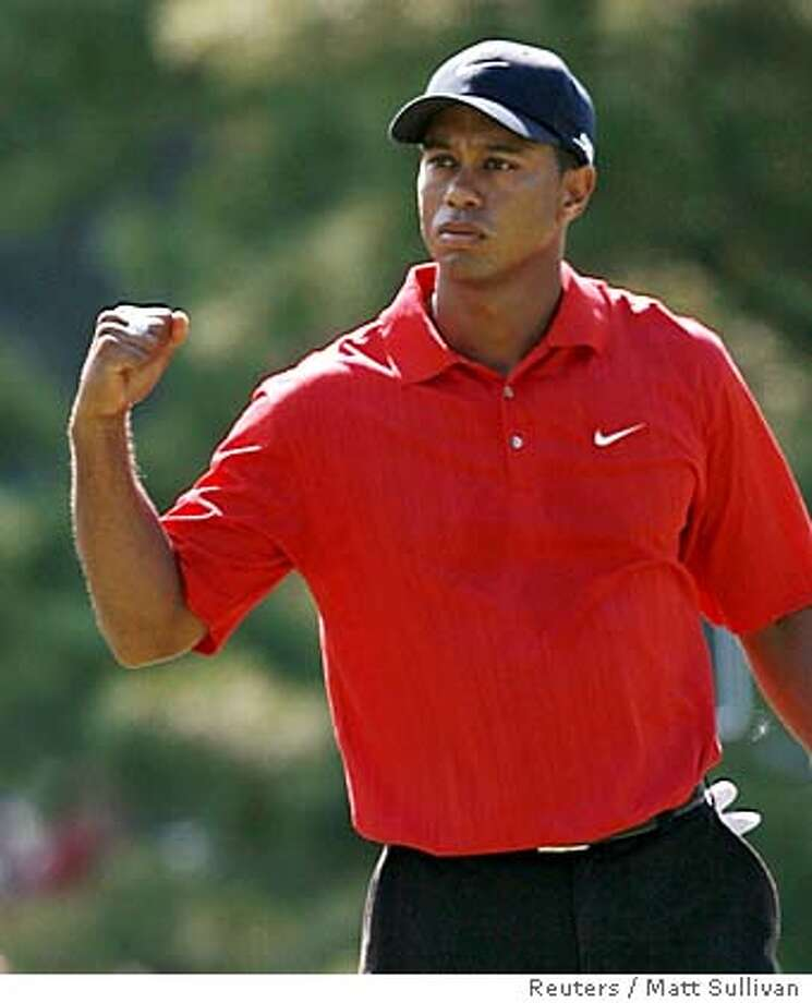 Tiger Woods reacts to his birdie putt on the eighth hole in the final round of the 88th PGA Championship golf tournament in Medinah, Illinois August 20, 2006. REUTERS/Matt Sullivan (UNITED STATES) Photo: MATT SULLIVAN