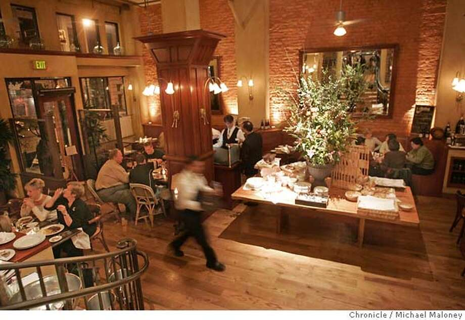 "Interior of the dining room with the dessert island.  Dining out photos for Cafe de la Presse in San Francisco. Please get the interior. Detail of the magazine rack. For food: the lamb stew; the monkfish with saffron sauce and the smoked salmon galette ""pizza."" Dessert: floating Island (could be individual or in the bowl displayed on the dessert table in middle of restaurant.  Event in San Francisco, CA  Photo by Michael Maloney / The Chronicle Photo: Michael Maloney"