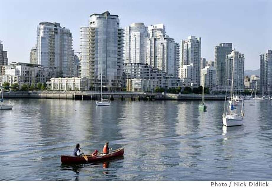 Canoeists paddle about on False Creek as Concord Pacific Place's buildings rise gradually from the waterfront. Photo by Nick Didlick, special to the Chronicle