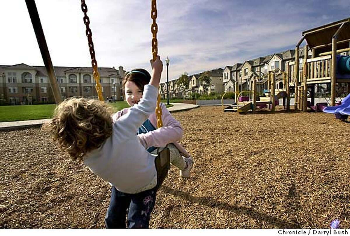 Local Bay Meadows residents, Julia Ratti, 3, rides on top of sister, Isabella, 5, back right, as mother Emily Ratti (not shown) takes the children to the playground and open park at corner of Yates Way and David St. with the new Bay Meadows housing development surrounding it. 1/23/04 in San Mateo. DARRYL BUSH / The Chronicle