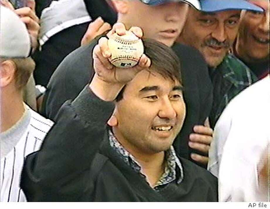 BONDSCATCH2-C-07OCT01-SP-KNTV11-This is a film grab of 36 year old Patrick Hayashi of Campbell holds up the ball hit by Barry Bonds for his 73rd homerun at Pac Bell Park on Sunday October 7, 2001.