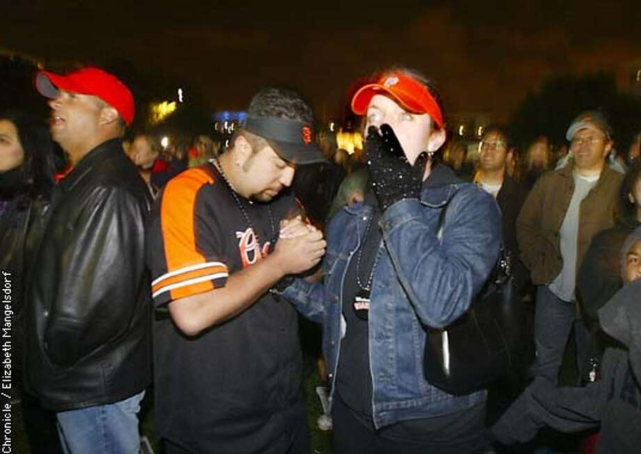 FANS27-C-26OCT02-MT-LM  Mario Alvarado prays as Carolyn Backer (center right) watches the last out as the Giants lose game 6 of the world series. They are at the big screen gathering at Yerba Buena center.  Chronicle photo/Liz Mangelsdorf